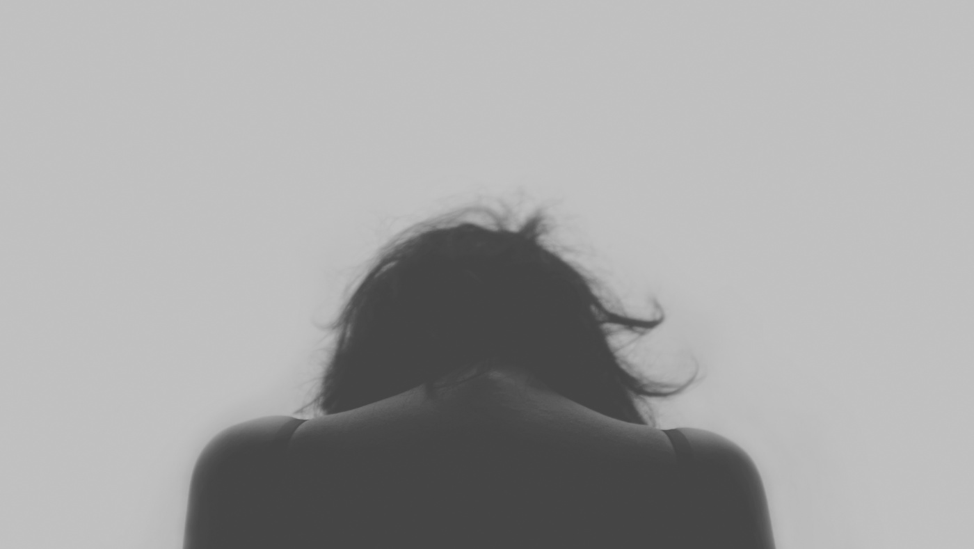Image Description: a silhouette of shoulders and hanging head facing a grey background