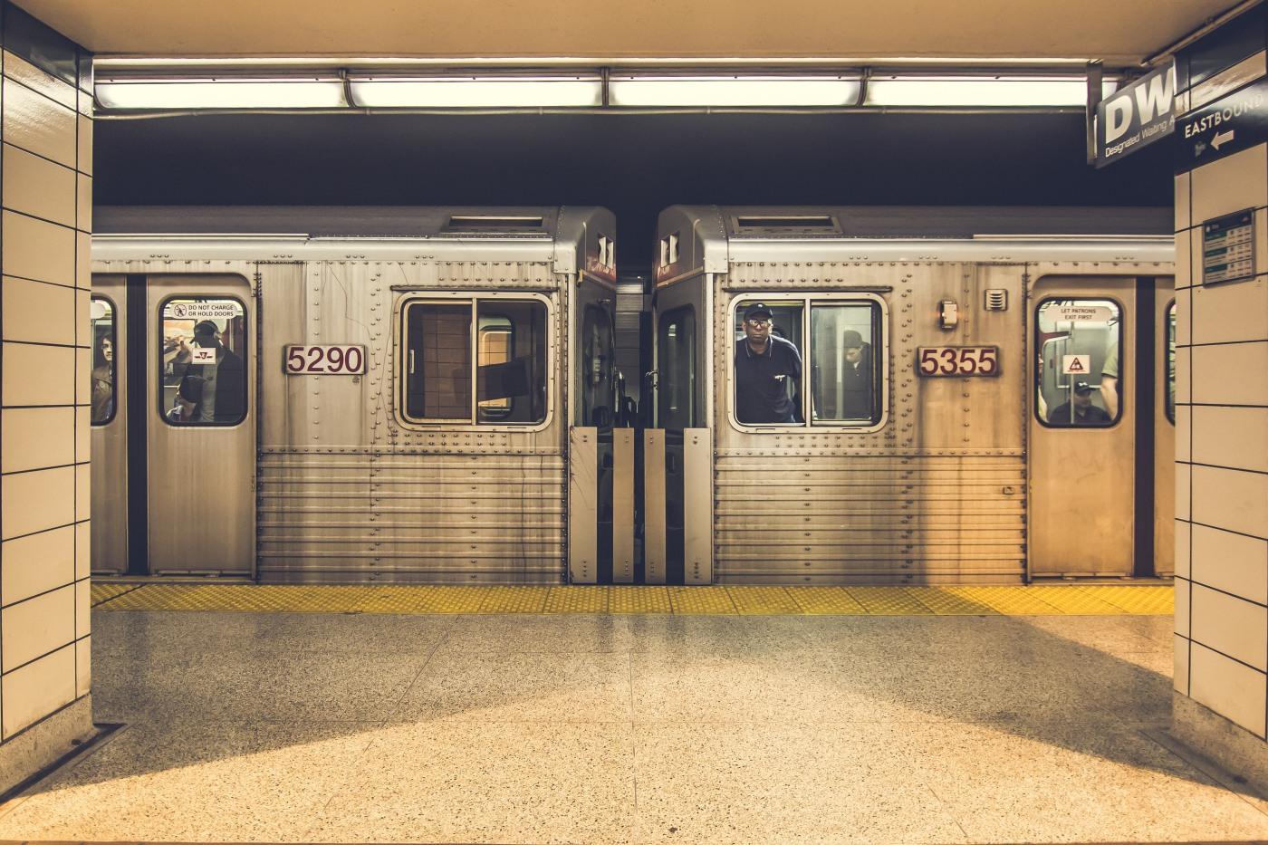 Image Description: An image of a hallway TTC hallway that looks onto a platform where an old TTC subway train waits